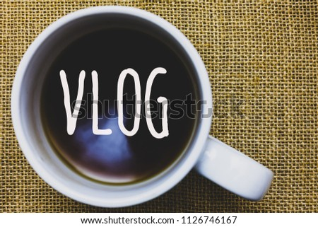 Handwriting text writing Vlog. Concept meaning Entertaining multimedia self broadcasting news reporting stories Mug coffee thoughts ideas creative inspirations nice mat black shadow.