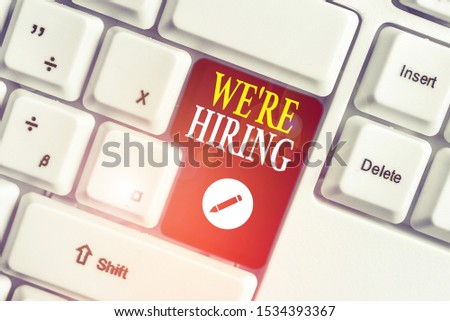 Handwriting text writing We Re Hiring. Concept meaning Advertising Employment Workforce Placement New Job White pc keyboard with empty note paper above white background key copy space.