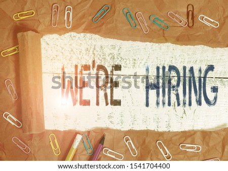 Handwriting text writing We Re Hiring. Concept meaning recently employ someone or pay him to do particular job Stationary and torn cardboard placed above a wooden classic table backdrop.