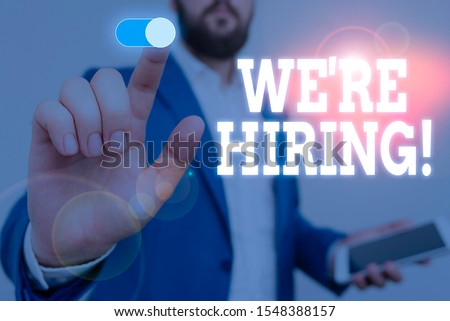 Handwriting text writing We Re Hiring. Concept meaning recently employ someone or pay him to do particular job Male human wear formal work suit presenting presentation using smart device.