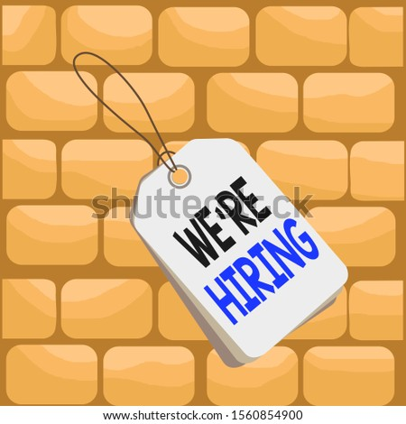 Handwriting text writing We Re Hiring. Concept meaning recently employ someone or pay him to do particular job Label rectangle empty badge attached string colorful background tag small.
