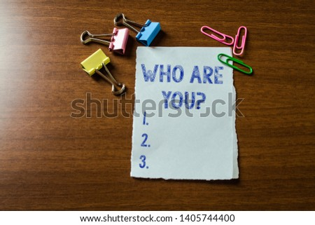 Handwriting text writing Who Are You Question. Concept meaning asking about someone identity or demonstratingal information Blank stationary paper set three colored clips binders lying wooden table.