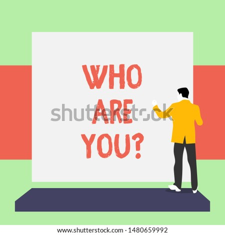 Handwriting text writing Who Are You Question. Concept meaning asking about someone identity or demonstratingal information Back view young man dressed suit standing platform facing blank rectangle.