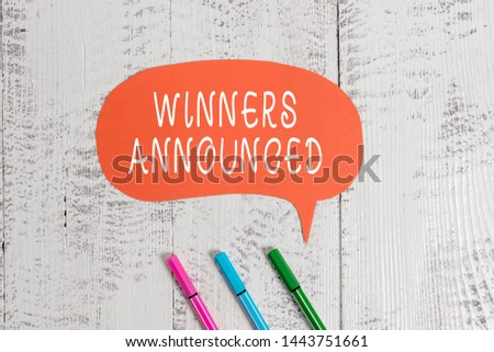 Handwriting text writing Winners Announced. Concept meaning Announcing who won the contest or any competition Ballpoints blank colored speech bubble wooden rustic vintage background.