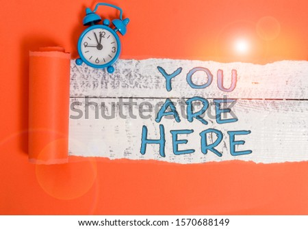 Handwriting text writing You Are Here. Concept meaning This is your location reference point global positioning system Alarm clock and torn cardboard placed above a wooden classic table backdrop. #1570688149