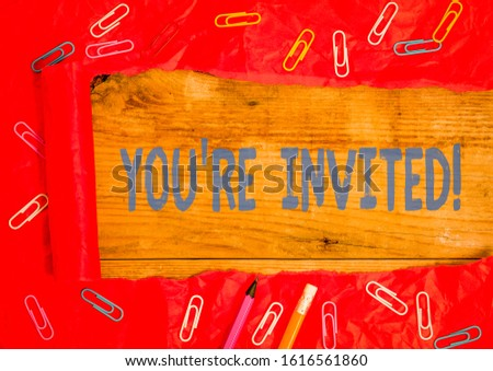 Handwriting text writing You Re Invited. Concept meaning make a polite friendly request to someone go somewhere Stationary and torn cardboard placed above a wooden classic table backdrop.