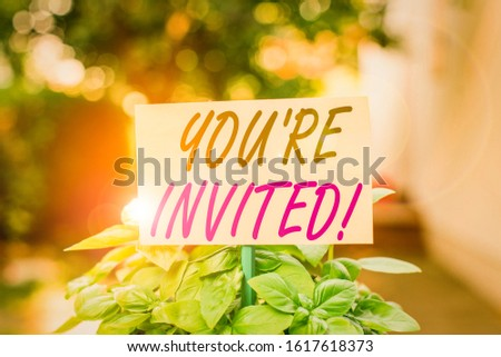 Handwriting text writing You Re Invited. Concept meaning make a polite friendly request to someone go somewhere Plain empty paper attached to a stick and placed in the green leafy plants.