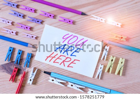Handwriting text You Are Here. Concept meaning This is your location reference point global positioning system Colored clothespin papers empty reminder wooden floor background office. #1578251779