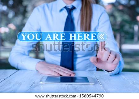 Handwriting text You Are Here. Concept meaning This is your location reference point global positioning system Female business person sitting by table and holding mobile phone. #1580544790