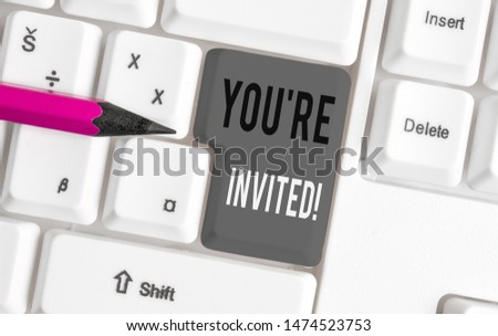 Handwriting text You Re Invited. Concept meaning make a polite friendly request to someone go somewhere White pc keyboard with empty note paper above white background key copy space. #1474523753