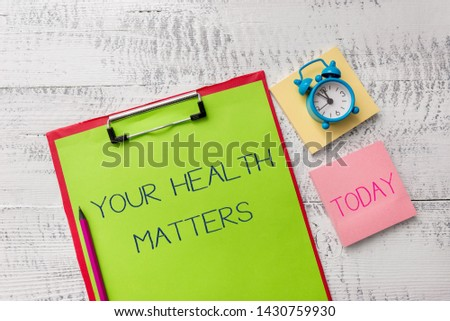 Handwriting text Your Health Matters. Concept meaning good health is most important among other things Metal clipboard sheets marker alarm clock notes pad wooden background.