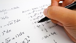 Handwriting to solve math formulas holding a computer pen. Math Formulas solves the test, practice, test or exam, background concept in math class.