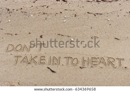 "Handwriting  words ""DON'T TAKE IN TO HEART."" on sand of beach."