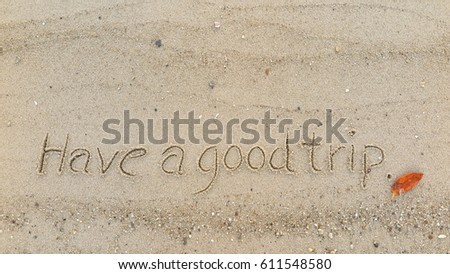 "Handwriting words ""Have a good trip"" on sand of beach"
