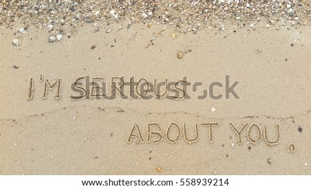 "Handwriting words ""I'M SERIOUS ABOUT YOU"" on sand of beach"