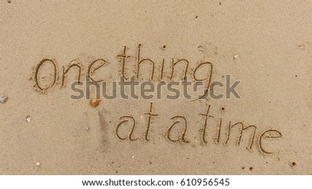 """Handwriting words """"One thing at a time"""" on sand of beach #610956545"""