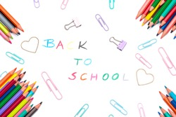 Handwritten back to school sign made of multicoloured pencil crayons. School supplies. Education concept. Colorful pencils, paperclips and paper clamps arranged on white background, top view