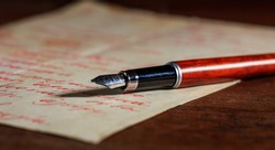 Handwritten letter and an ink pen on a wooden table