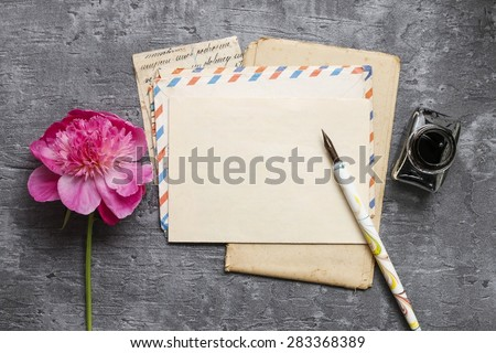 Handwritten letters and pink peonies on grey background, copy space