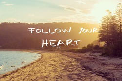 Handwritten text over sunset calm sunny beach background, FOLLOW YOUR HEART, vintage filter applied, motivational concept image
