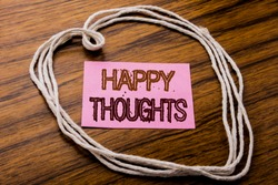 Handwritten text showing Happy Thoughts. Business concept for Happiness Thinking Good written on sticky note paper on dark wooden background. With heart meaning love or adoration.