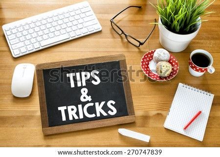 Handwritten tips & tricks on blackboard. Handwritten tips & tricks with chalk on blackboard, keyboard,notebook,glasses,cup of coffee,baking and green plant on wooden background