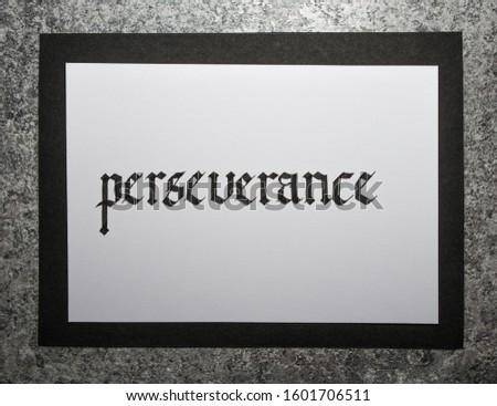 Handwritten word Perseverance, gray stone background. Gothic script calligraphy.