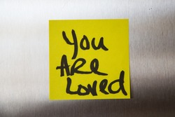 Handwritten yellow sticky love note a message You Are Loved stainless steel refrigerator door gradation background daily affirmation affirmations meditation positive thinking thoughts attitude routine