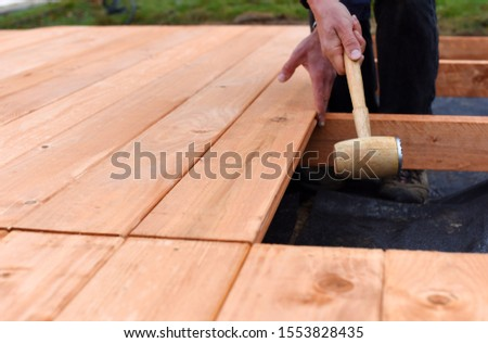 Handy carpenter installing wooden planks during flooring works outside the new house. Czech republic, Europe.