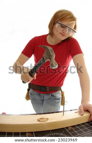 Handy girl gets ready to hammer a nail into a piece of wood.