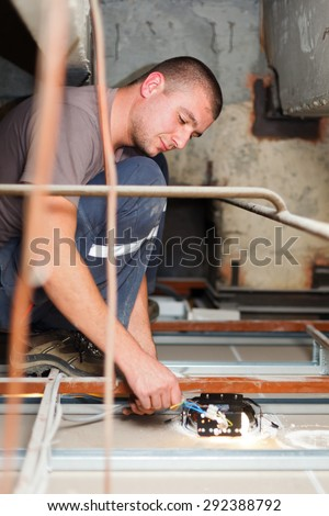 Handy man electrician assembling light working with cables.