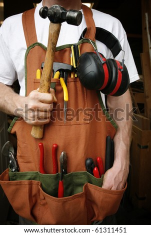 Handy man in front of work shop holding hammer
