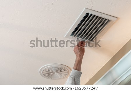 Handyman adjusting HVAC ceiling air vent. Air flow adjustment for overhead home heat and air conditioning ventilation duct. Photo stock ©