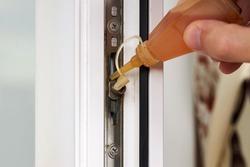 handyman adjusting white pvc plastic window indoors. worker using grease lubricant to repair upvc window. homework maintenance.