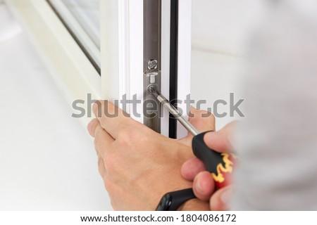 handyman adjusting white pvc plastic window indoors. worker using screwdriver to repair upvc window. homework maintenance. Stock photo ©