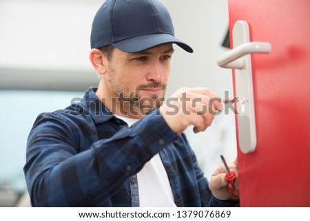 handyman fixing the door with screwdriver
