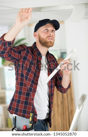 handyman holding a replacement fluorescent bulb