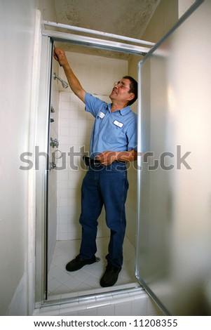 Handyman in blue shirt fixing shower - stock photo