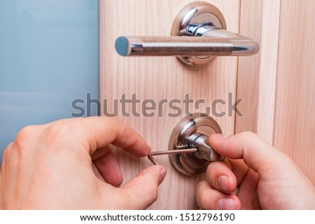 Handyman is repairing an interior door lock. Man fixing lock with L-Shaped Hex Wrench. Stock fotó ©