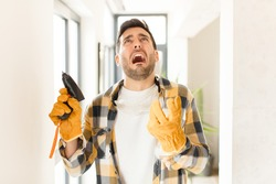 handyman looking desperate and frustrated, stressed, unhappy and annoyed, shouting and screaming