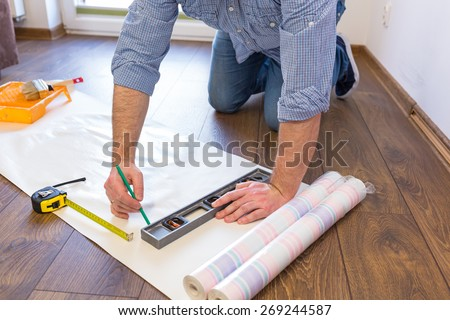 Handyman measuring wallpaper to cut #269244587