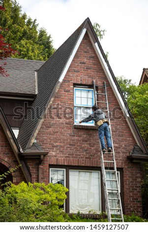 Handyman on a ladder painting the windowsill of an old brick house, in a home remodel scene with space for text on top and bottom