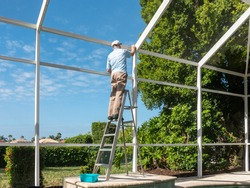 Handyman on ladder cleaning outdoor pool cage enclosure. Screened swimming pool lanai maintenance and screen repair.