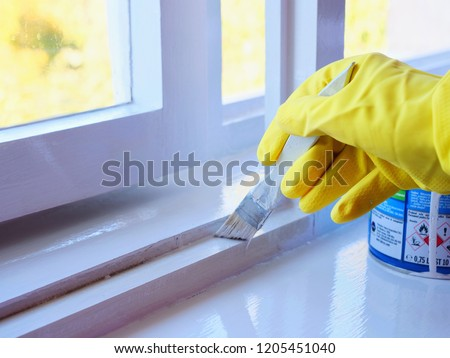 Handyman paints a window frame with white paint with a paint brush. Hand in yellow rubber gloves applies a glossy paint finish to window casement. Foto d'archivio ©