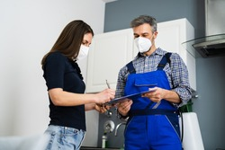 Handyman Plumber And Customer With Service Contract On Clipboard In Face Mask