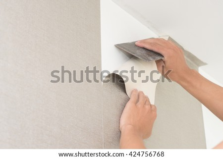 Handyman putting up wallpaper on the wall #424756768