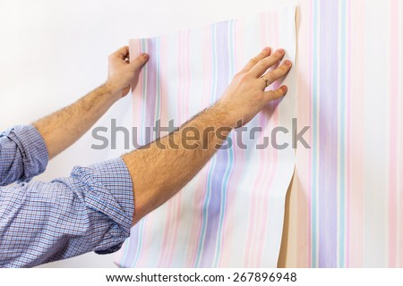 Man putting up wallpapers