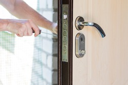 Handyman repair and installing the lock in the metal front door in house.
