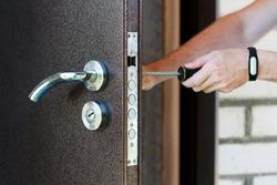 Handyman repair the door lock in metal entrance door, Man fixing lock with screwdriver, Close-up of repairing door, professional locksmith installing new deadbolt lock on house