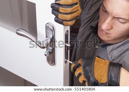 Shutterstock handyman repair the door lock in the room